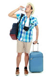 Tired traveler. Tired young traveler drinking a bottle of water Royalty Free Stock Image