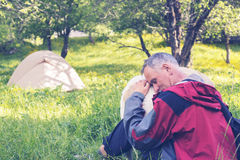 Tired traveler hugs his dog, sitting next to the tent Stock Photos