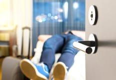 Tired traveler sleeping on hotel room bed. Stock Photos