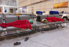 Tired travelers sleeping on the airpot departure gates bench. Mother and daughter sleeping on the airpot departure gates bench. Tireing travel concept stock image