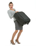 Tired traveling woman raising suitcase Royalty Free Stock Image