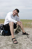 A tired traveller sits on his back pack Stock Photography