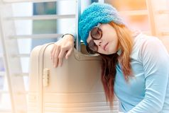 Tired traveller tourist woman sleeping on luggage while waiting Stock Photo