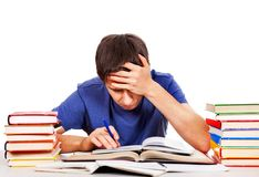 Tired Student with a Books. Tired and Troubled Student at the Writing Table on the White Background Stock Photo