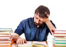 Tired Student with the Books. Tired and Troubled Student at the Writing Table on the White Background Royalty Free Stock Image