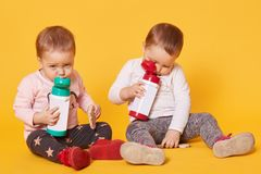 Tired twin sisters sits on the floor while eating and drinking. Cute playful children are bored in the middle of the day. Little stock image