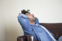 Tired or unhappy Asian man sitting on sofa holding head. Stock Photos