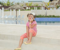 tired unhappy child girl with painted face sitting on concrete steps near the swimming pool in background Stock Image