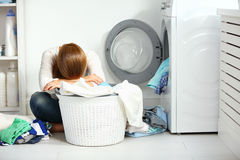Tired unhappy woman housewife  fold clothes into the washing mac Royalty Free Stock Photos