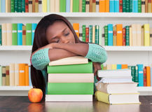 Tired University Student Sleeping On Books In Library. Tired university student sleeping on stacked books at desk in library royalty free stock images