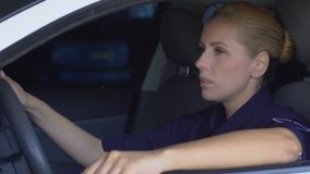 Tired upset female cop sitting in patrol car, pondering difficult investigation stock video
