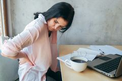 Tired upset young businesswoman suffering from strong chronic backache or osteochondrosis at work, stressed student girl feels. Pain in aching back.Teenager stock photography