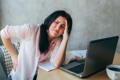 Tired upset young businesswoman suffering from strong chronic backache or osteochondrosis at work, stressed student girl feels. Pain in aching back.Teenager stock photos