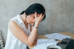 Tired upset young businesswoman suffering from strong chronic headache migraine or memory loss at work, stressed dizzy fatigued. Student girl feels pain in royalty free stock photo