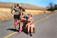Tired of waiting. Three unhappy sexy party girls are tired of waiting for a ride, wearing short shorts and high heels are hitch hiking with their luggage on a Royalty Free Stock Photo