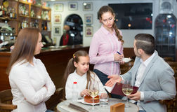 Tired waitress and displeased family Royalty Free Stock Image