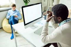 Tired White Collar Worker Using Computer. Back view of tired white collar worker rubbing his temples while sitting in front of computer, interior of modern open Royalty Free Stock Images