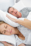 Tired wife blocking her ears from noise of husband snoring. In bedroom at home Stock Images