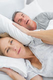 Tired wife blocking her ears from noise of husband snoring looking at camera. In bedroom at home royalty free stock image