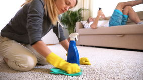 Tired wife cleans carpet while her husband lies on the couch with the phone. stock video