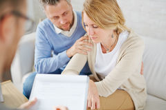 Tired wife. Man supporting his unhappy wife during visit to psychologist stock image