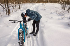 Tired Winter Cyclist. A picture of a cyclist leaning over his bike from fatigue after biking up a hill on a snowshoe trail