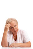 Tired woman. Portrait of sick aged woman touching head and looking at camera Royalty Free Stock Images