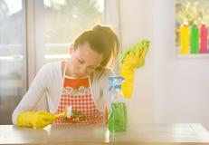 Woman scrubbing desk Stock Images