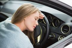 Tired woman asleep on steering wheel Stock Photo