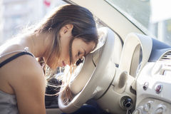 Tired woman asleep on steering wheel in her car. Stress concept Stock Image
