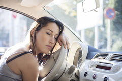 Tired woman asleep on steering wheel in her car Stock Image