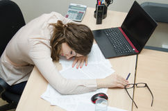 Tired woman asleep on a workplace at office Stock Image