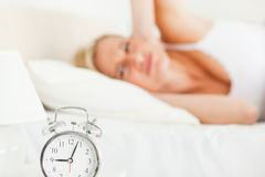 Tired woman awaked by her alarm clock Royalty Free Stock Photos