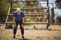 Tired woman bend down with hands on knees during obstacle course Royalty Free Stock Photography