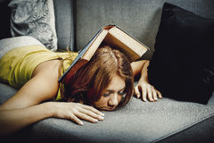 Tired woman with book on head. Stock Image