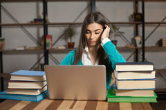Tired woman with books. Woman with lots of books and laptop is sitting at the wood table Royalty Free Stock Image