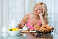 Tired woman at breakfast Stock Images