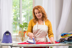 Tired woman busy with housework at home. Housewife ironing clothes for her family Royalty Free Stock Photos