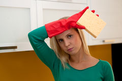 Tired woman cleaning kitchen. Wearing red gloves Stock Photo