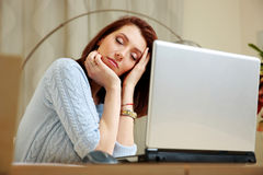 Tired woman with closing eyes sitting on her workout. At home royalty free stock photo