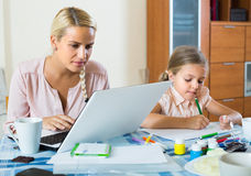 Tired woman with daughter working online Royalty Free Stock Image