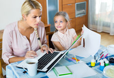 Tired woman with daughter working online Royalty Free Stock Photography