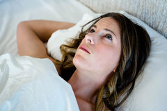tired woman daydreaming in her bed Royalty Free Stock Images