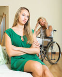 Tired woman and disabled person Royalty Free Stock Photo