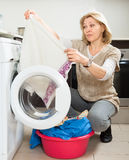 Tired woman doing laundry with washing machine Stock Image