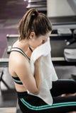 Tired woman on drawing machine wiping sweat Stock Photo