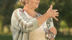 Tired woman drinking water from bottle after outside workout, aqua balance. Stock footage stock footage
