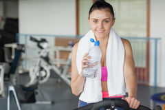 Tired woman drinking water while working out at spinning class Stock Photography