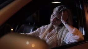 Tired woman driver sitting in car at night. Slow motion stock video footage