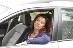 Tired woman driver sleeps in car Stock Image